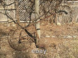 Antique iron cultivator plow walk-behind farm implement